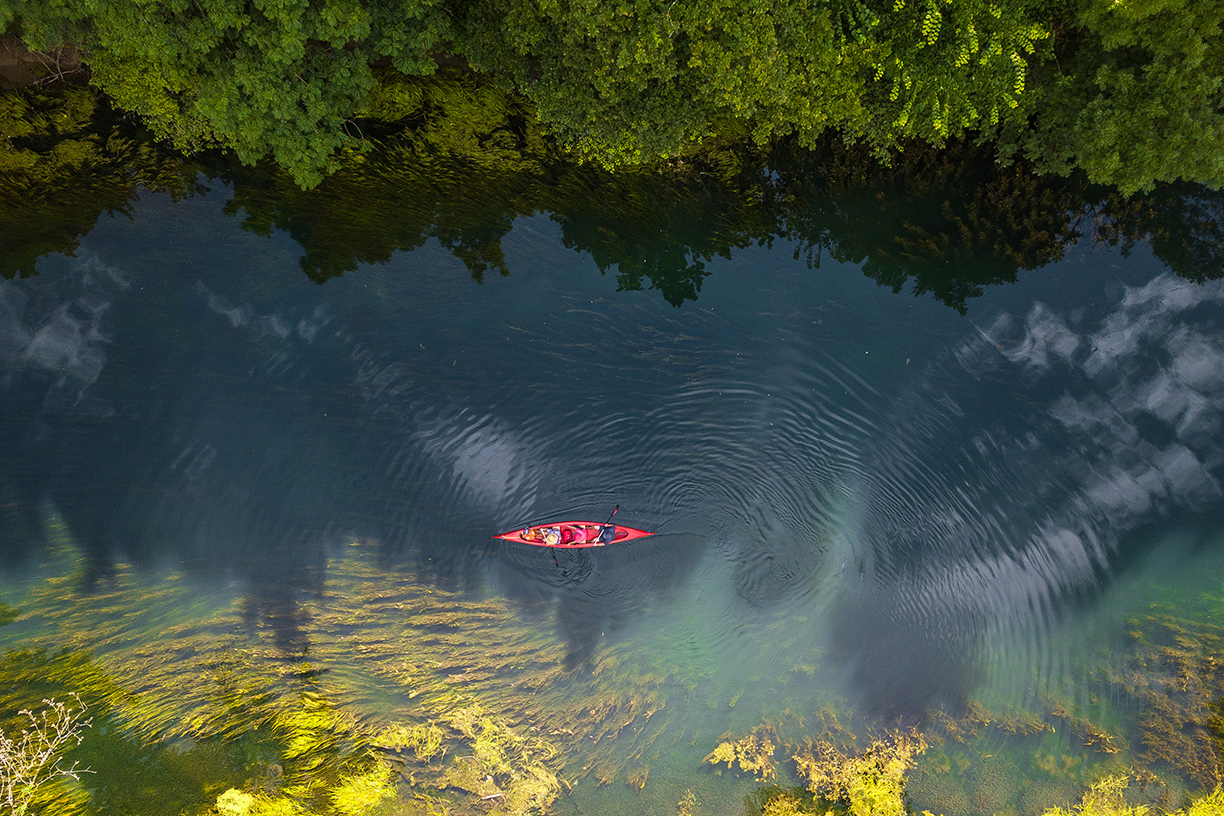 aerial view of river and canoeist